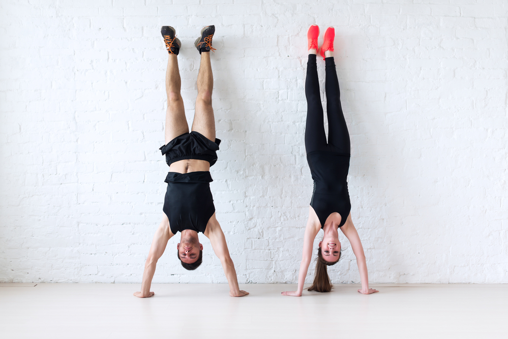 sportsmen woman and man doing a handstand against wall